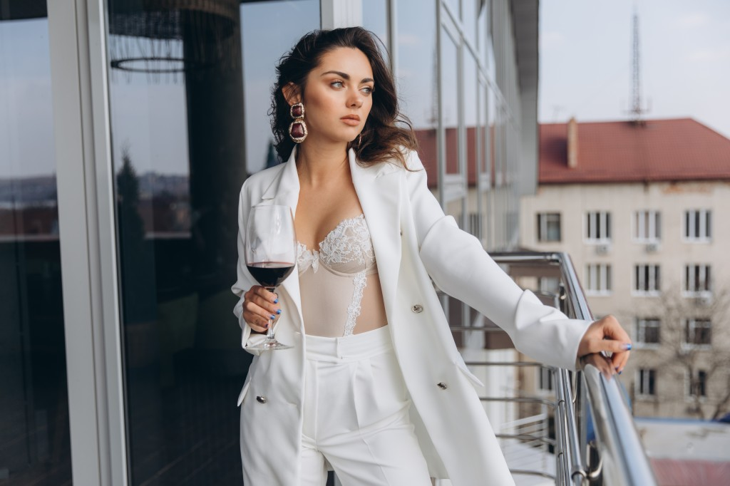 Young beautiful sexy woman in white corset and jacket relaxing at balcony with a view to the urban landscapes and drinking red wine.