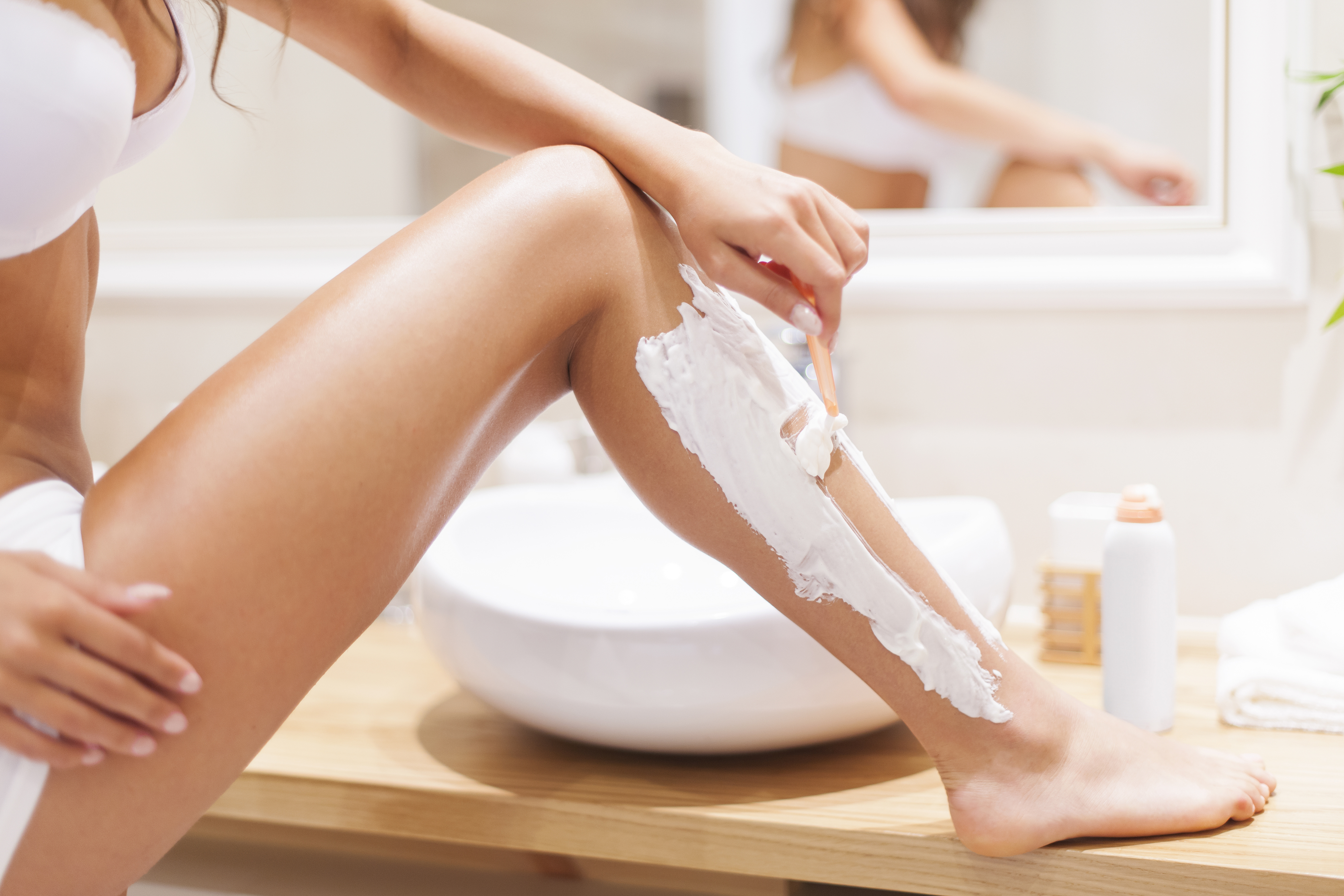 Close up of woman shaving legs in bathroom