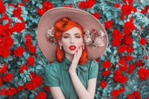 Valentines Day background. Fabulous retro girl with red lips in mint dress on awesome summer background. Woman portrait. Awesome redhead model expresses emotions on background of roses bush.