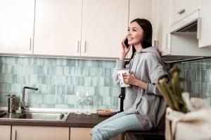 Dark-haired woman wearing oversize hoodie sitting near sink